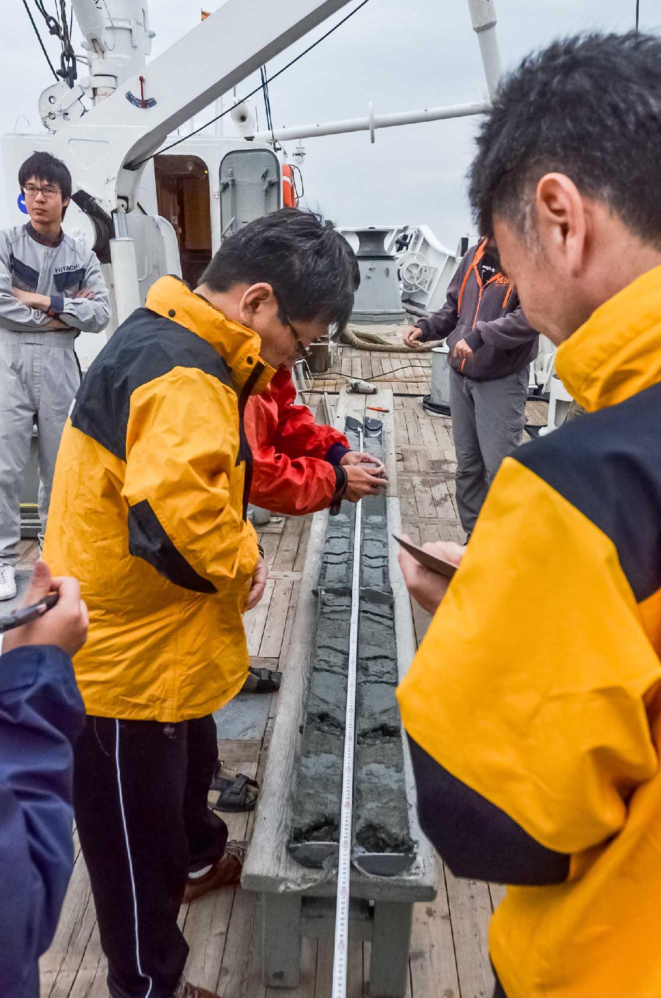 Японские ученые изучают геологический разрез по керну из трубы.